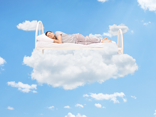 The Importance of Sleep in Recovery - man sleeping on bed in clouds