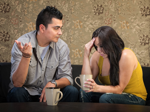 What Not to Do When Someone Comes Home from Rehab - man and woman drinking coffee disagreeing