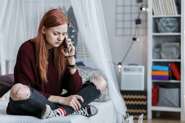 Drug Slang and Warning Signs - young red haired girl sitting on bed talking on cell phone