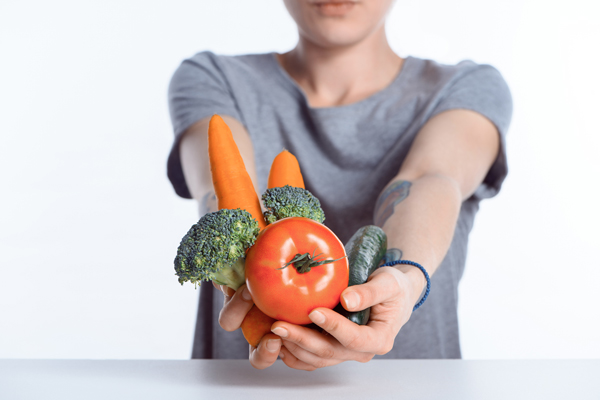 Foods Your Body Needs in Recovery - woman holding out fresh vegetables