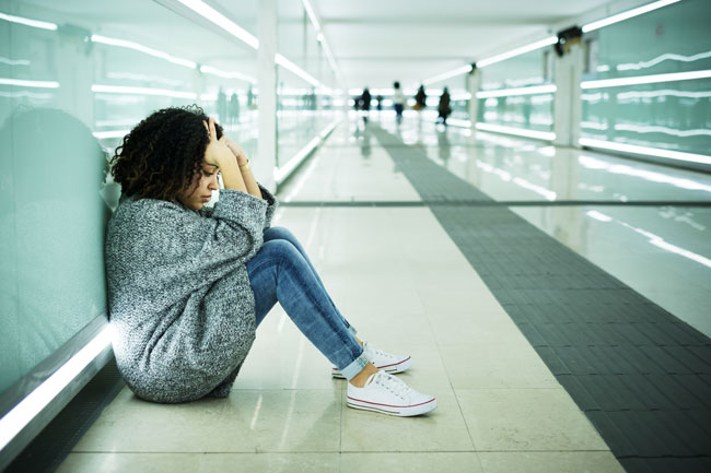 Signs-Your-Teen-Is-Using-Drugs-and-Alcohol - young upset girl sitting at airport or station