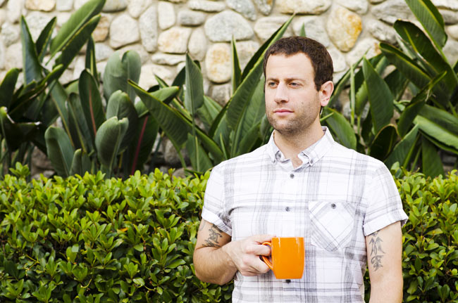 man outside drinking coffee