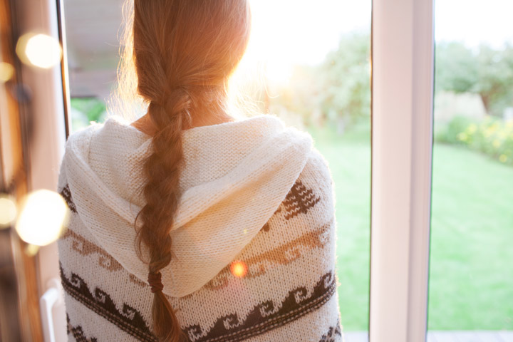 woman looking out window at beautiful sunshine