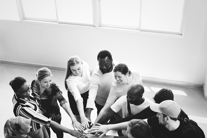black and white image of people putting hands in circle