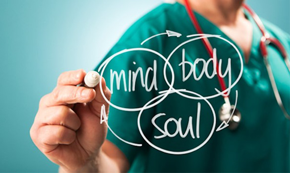 clinician or doctor wearing scrubs writing mind body soul on a transparent board