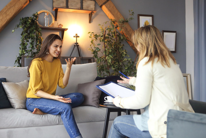 young woman having counseling session with female therapist in lovely office - cognitive behavioral therapy