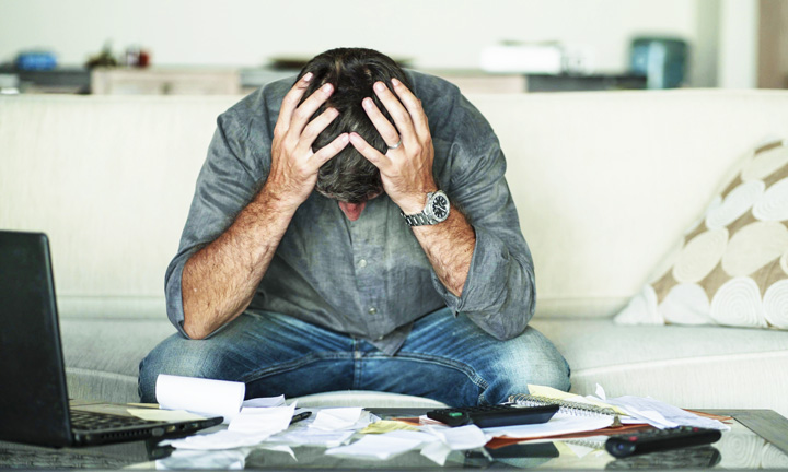 stressed out man with head in hands surrounded by papers - financial