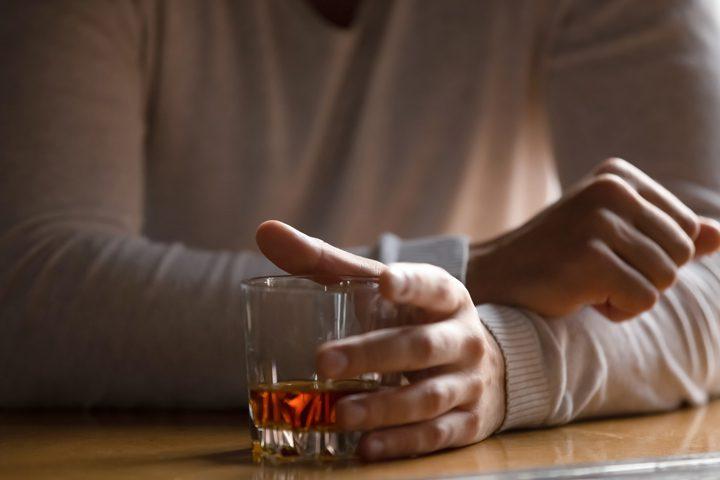 closeup of man sitting with tumbler of liquor - alcoholism