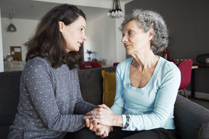 middle age woman having serious conversation with her senior mother - parent