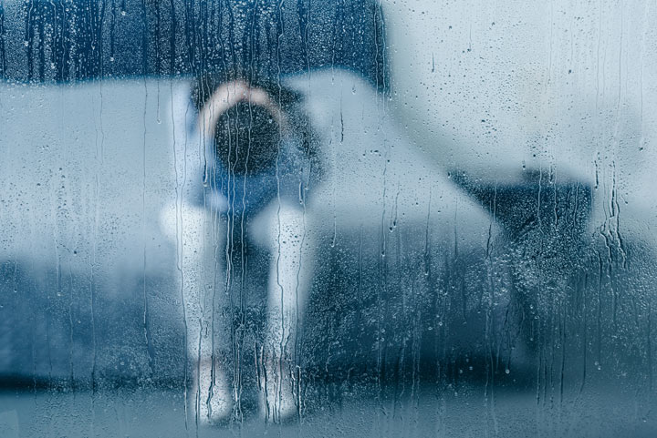 depressed woman sitting on bed, seen through rainy window - co-occurring disorders