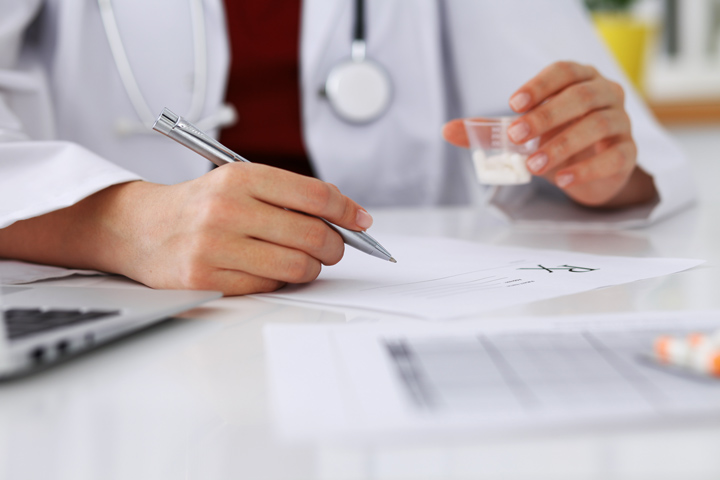 doctor writing prescription and holding cup of pills - professionals treatment program