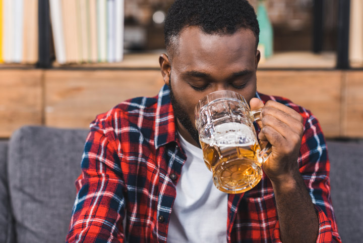 young African American man in plaid shirt drinking a beer from a glass mug - alcohol detox
