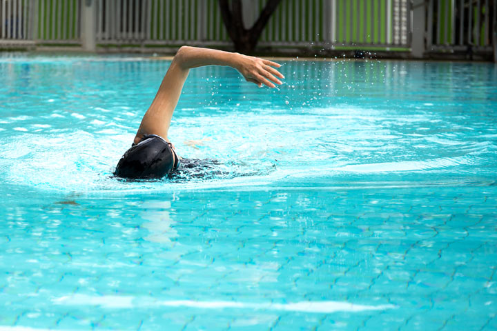 person swimming in outdoor pool - exercise