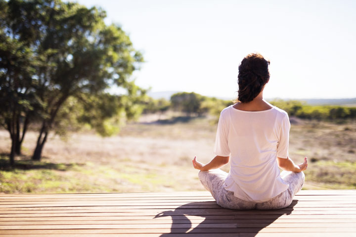 woman sitting outside in lotus position with her back to the camera - meditation and pain