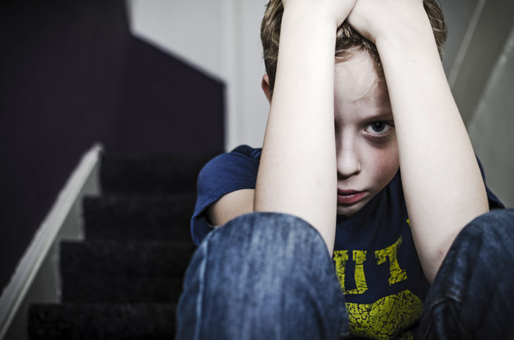 sad little boy sitting on steps with arms covering most of his sad face - past trauma, childhood trauma