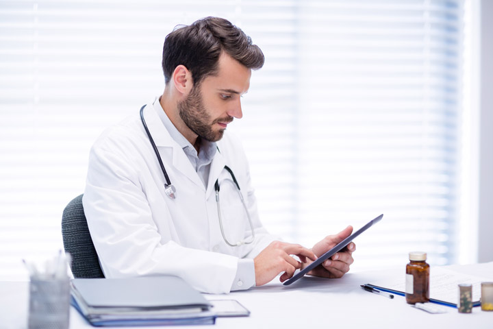 handsome young male doctor using tablet computer at his desk - benzo addiction