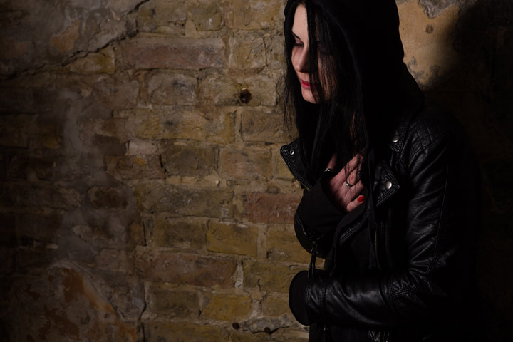 dark haired young woman in black leather jacket looking sick or upset in alley - meth
