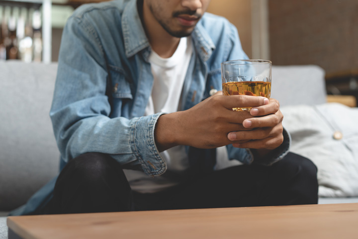 man in his early thirties sitting at home drinking liquor - alcohol consumption