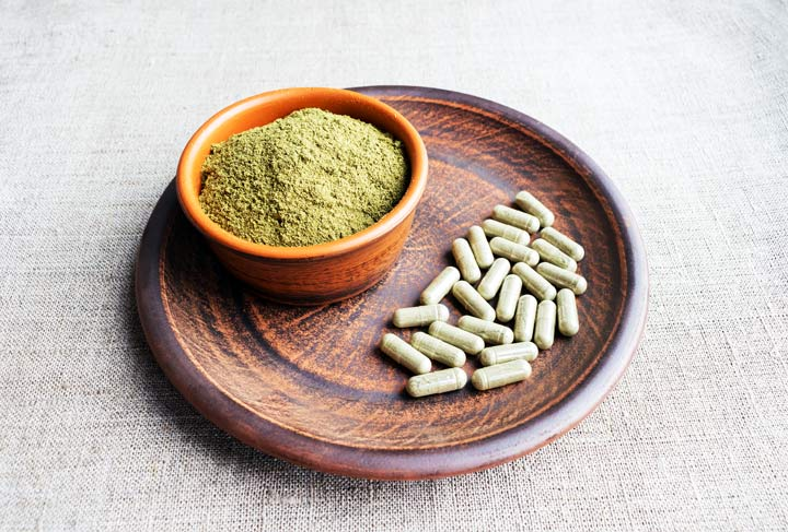 wooden plate and bowl with kratom powder and capsules - kratom addiction